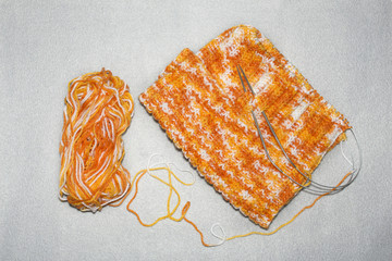 the process of knitting the cap with a pattern of the riffle, a melange thread of a white-yellow-orange color