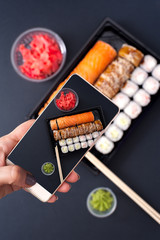 Popular Japanese food - Sushi rolls set with wasabi, ginger and chopsticks, top view. Female holding smartphone and doing picture of food.
