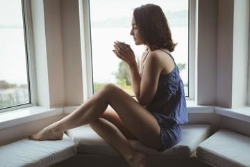 Woman having cup of coffee near window