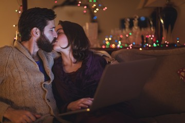 Couple kissing each other while using laptop in living room