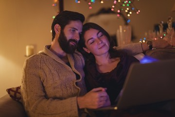 Smiling couple using laptop in living room