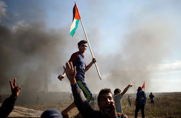 A protester holds a Palestinian flag during clashes with Israeli troops near the border with Israel in the east of Gaza City