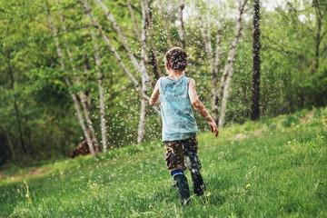 Boy running through a sprinkler in the garden