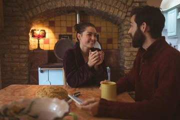 Couple interacting with each other while having cup of coffee