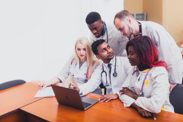 A group of mixed-race physicians discusses the diagnosis behind a laptop in the office. In the background, the asian professor explains to students the physicians anatomy