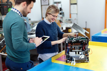 Young students of robotics preparing robot for testing