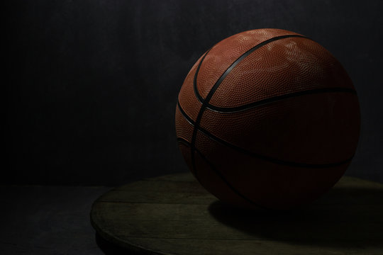 Old faded basketball on a round wooden table. Beautiful background.