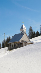 A small mountain church with allaround white snow and blue sky