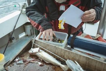 Fisherman maintaining record of hand tool