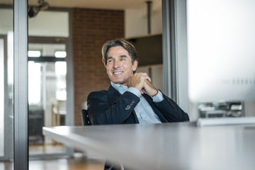 Smiling businessman sitting at table in office
