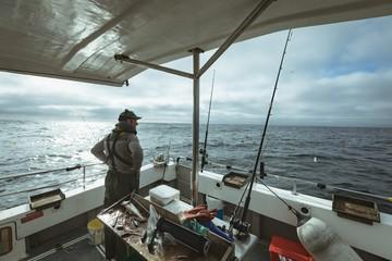 Fisherman standing on boat