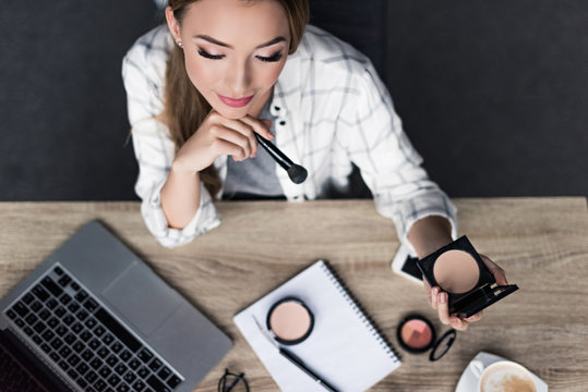 top view of thoughtful young woman doing makeup at workplace
