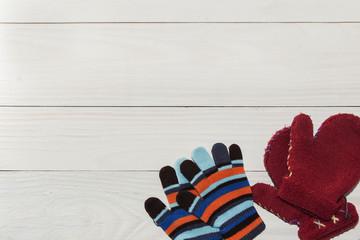 Winter children's mittens lie on a wooden background