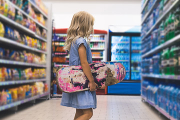 blonde kid with skateboard standing in supermarket with shelves behind