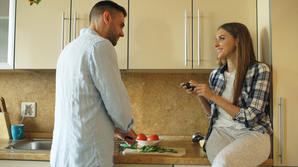 Attractive couple cooking in the kitchen and taking photo using smartphone fo sharing social media at home