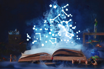 Book of spells with mystical smoke and stary sky. Magical still life with jars and bottles on a dark background. Witch workplace concept.