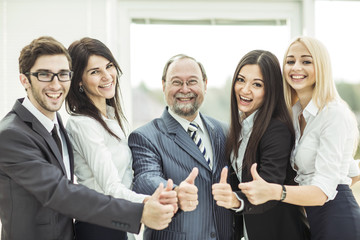 concept of victory: friendly business team makes a gesture of thumbs up.