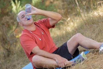 senior jogger drinking water