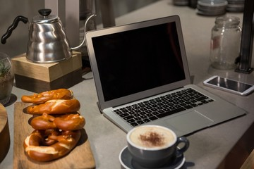 Close-up of coffee, laptop and pretzel at counter