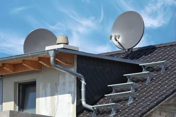 Satelliten-Antenne, Schornstein, Dachtreppe und Gaube auf einem Rohbau-Dach mit offener Balkendecke
