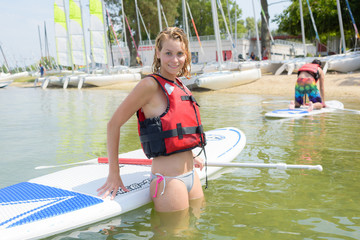 young blonde female posing against a paddleboard on lake
