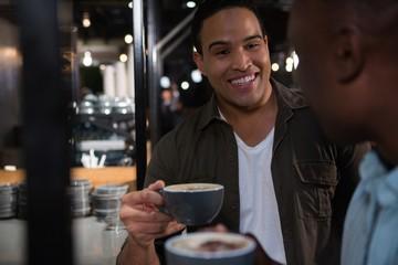 Happy man interacting while having coffee