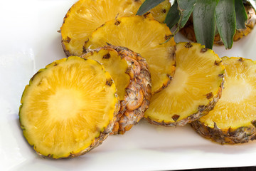 Pineapple slices with peel in white dish on wooden background