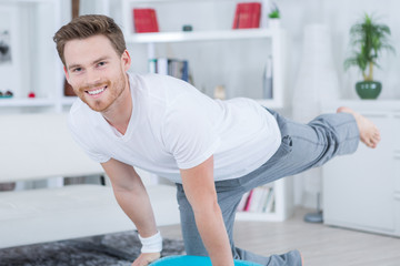 young man in lounge room doing exercise