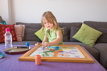 four years old blonde child with green sleeveless shirt sitting on brown sofa, playing parcheesi or parchisi or parchis, on table