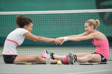 two attractive female tennis players stretching at the court
