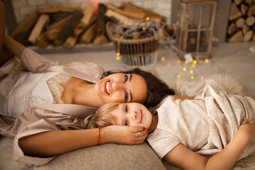 Mother with her daughter lies on floor and smiles. Side view.