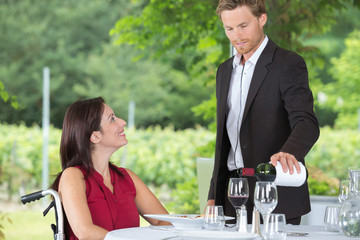 smiling woman in a wheelchair talking to waiter
