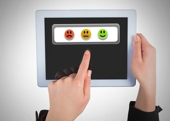Hand holding tablet with smiley face feedback satisfaction