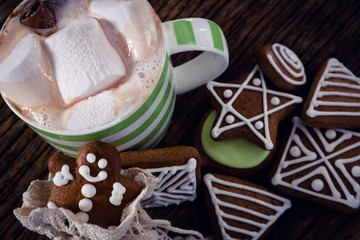 Various cookies and hot chocolate on wooden plank