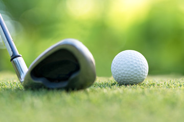 Golf club hitting golf ball along fairway towards green with copy space, green nature background.  Lifestyle Concept.  select focus