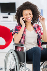 disabled woman in wheelchair using mobile phone at home