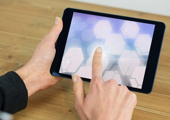 Hand touching glowing shapes on tablet