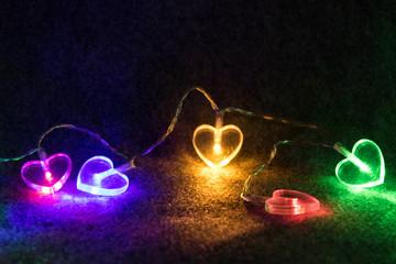 Lichterkette mit bunten Herzen - Romantisch vor schwarzem Hintergrund
