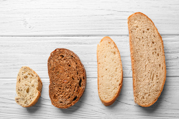Slices on different fresh yummy bread on wooden background