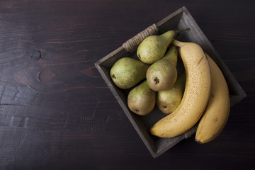 Bananas and pears in a wooden box