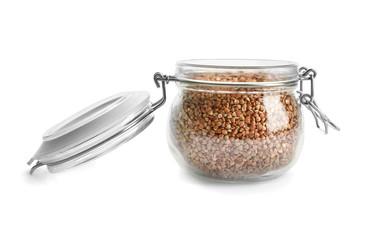 Jar with raw buckwheat on white background