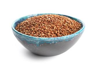 Bowl with raw buckwheat on white background