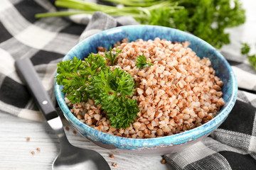 Bowl with cooked buckwheat on table