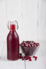 Cranberry juice in a bottle and a cranberries in a glass bowl