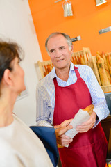 Baker serving baguette to customer