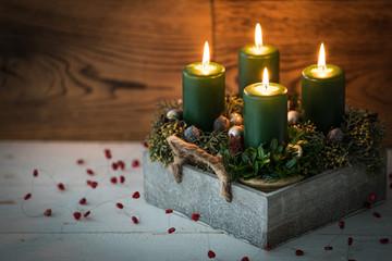 Adventsgesteck mit vier brennenden Kerzen auf weißem Holztisch