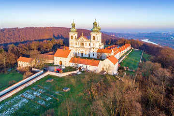 Camaldolese monastery and baroque church in the wood on the hill in Bielany, Krakow, Poland , Aerial view in sunset light with Vistula River and far view of Cracow city in the background