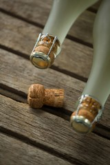 Bottles of champagne and its cork on wooden surface