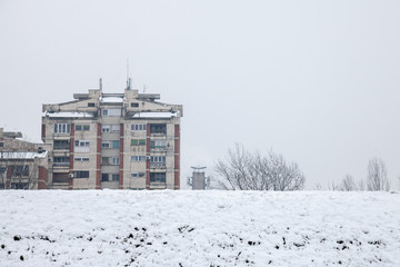 Communist housing buildings in front of a frozen hill in Pancevo, Serbia, during a afternoon with snow. This kind of towers are a symbol of Socialist architecture