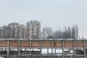 Communist housing buildings in front of an abandoned warehouse in Pancevo, Serbia, during a cold afternoon under the snow. This kind of towers are a symbol of Socialist architecture
